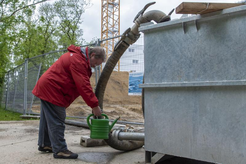 Een buurtbewoner tapt grondwater af op de werf bij stadsschool Het Tandwiel.