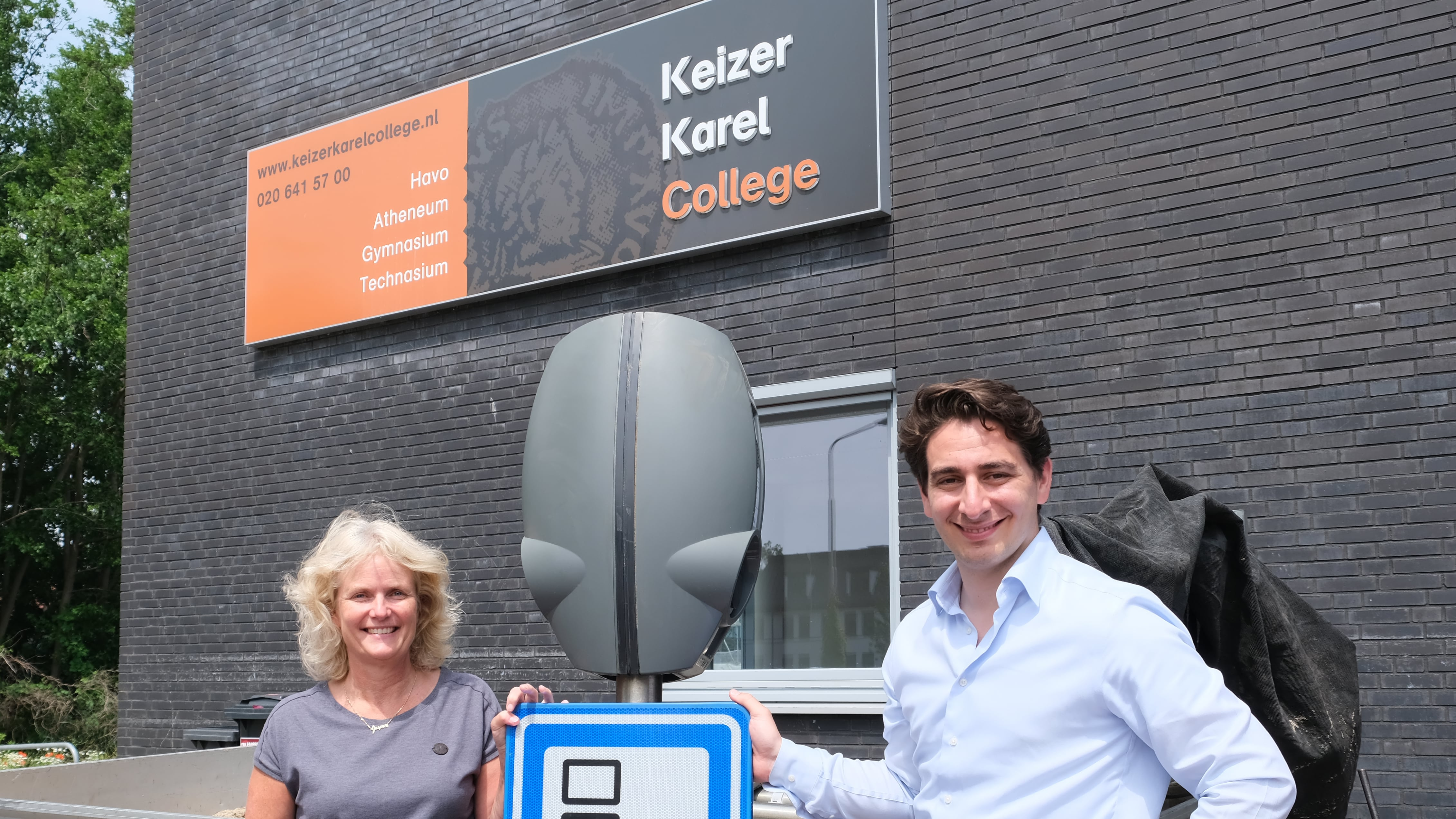 Maxime van Gelder, Business Development Manager Benelux bij EVBox en oud-leerling, overhandigde de laadstations aan Sietske Roos, technator en docent Nederlands op het Keizer Karel College in Amstelveen