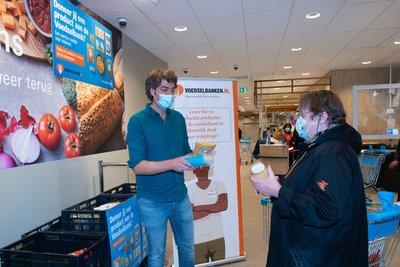 Frank Dane, ambassadeur van de Voedselbank, neemt de eerste donatie aan van een klant van Albert Heijn. Foto AH_Yasmin Hargreaves