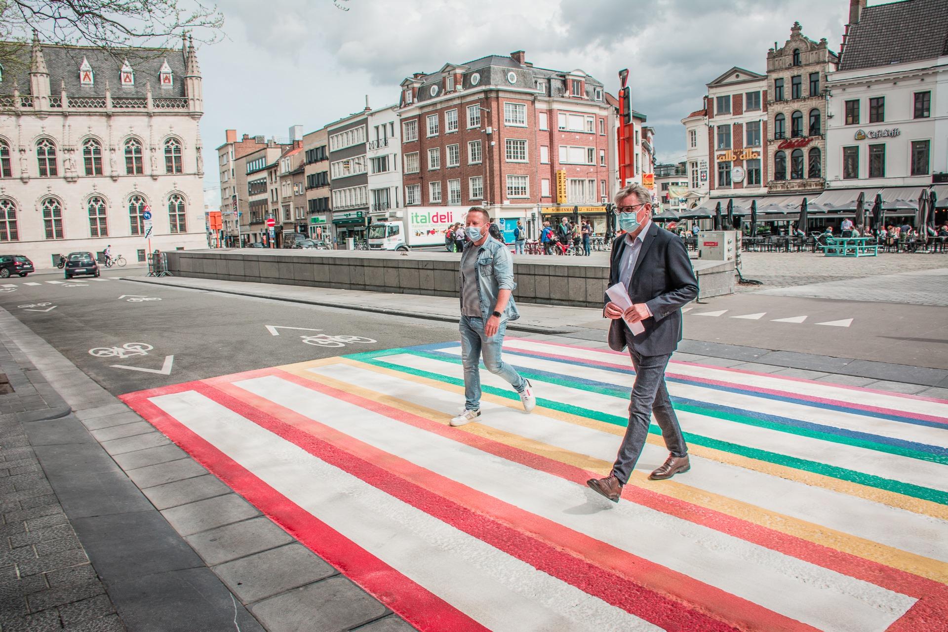 Schepen Axel Weydts en schepen Philippe De Coene wandelen het regenboogzebrapad in. (copyright: Kortrijk)